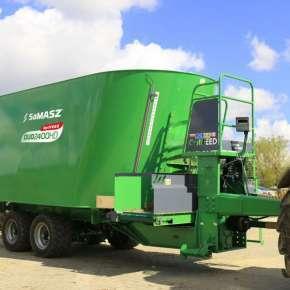 Zielony wóz paszowy dwuślimakowy DUO HD na osi Tandem firmy Samasz podczepiony do czerwonego ciągnika czeka na załadunek kiszonki www.korbanek.pl