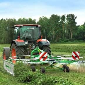 Czerwony traktor rolniczy zagrabia skoszoną koniczynę z trawą na łące za pomocą zielonej zgrabiarki zawieszanej Z-410 Samasz www.korbanek.pl