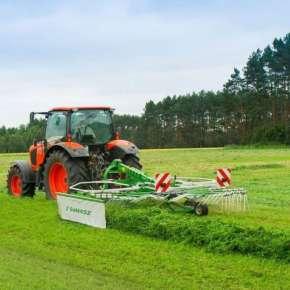 Czerwony ciągnik rolniczy z zieloną zgrabiarką zawieszana Z-410 firmy Samasz zgrabia skoszoną trawę www.korbanek.pl