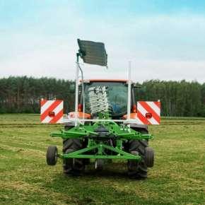Zielona zgrabiarka zawieszona i złożona do pozycji transportowej na czerwonym ciągniku www.korbanek.pl