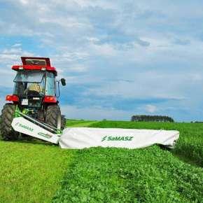 Traktor w kolorze czerwonym z kosiarką dyskową SAMBA 280 firmy Samasz kosi łąkę www.korbanek.pl