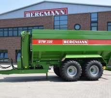 Przed budynkiem produkcyjnym firmy Bergmann stoi przyczepa do przeładunku zboża typ GTW koloru zielonego z napisem GTW Bergmann