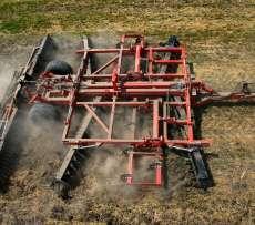 Półzawieszana brona talerzowa Gregoire Besson w pracy polowej na ściernisku zaczepiona do ciagnika rolniczego