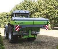 Zielony rozsiewacz zawieszany do nawozu MXL 1600 firmy UNIA Brzeg zawieszony na ciągniku rolniczym korbanek.pl