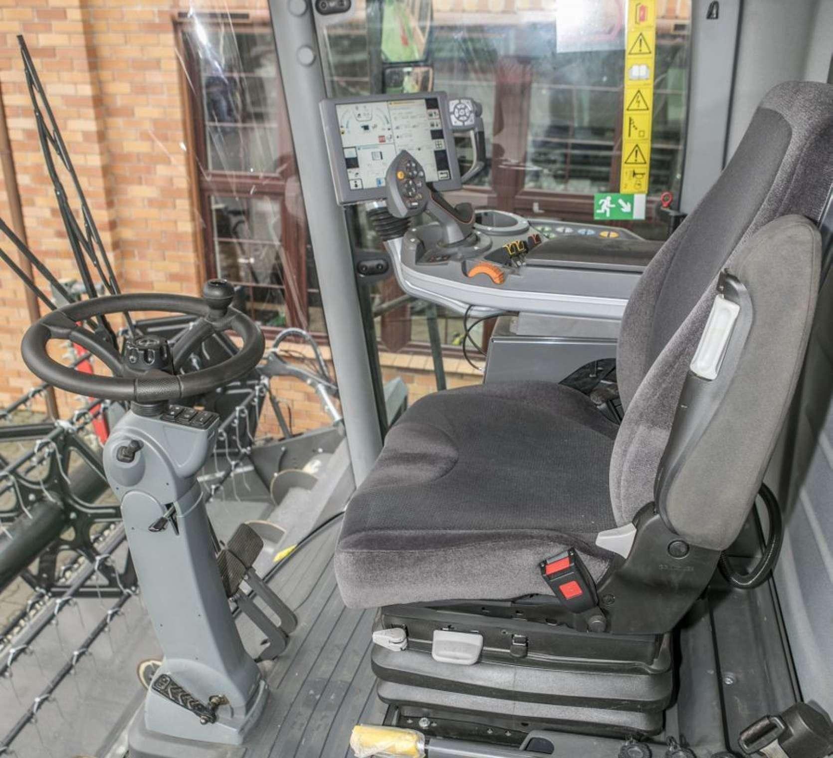 Wnętrze kabiny używanego kombajnu Fendt 6335 widok na kierownice i siedzenie operatora