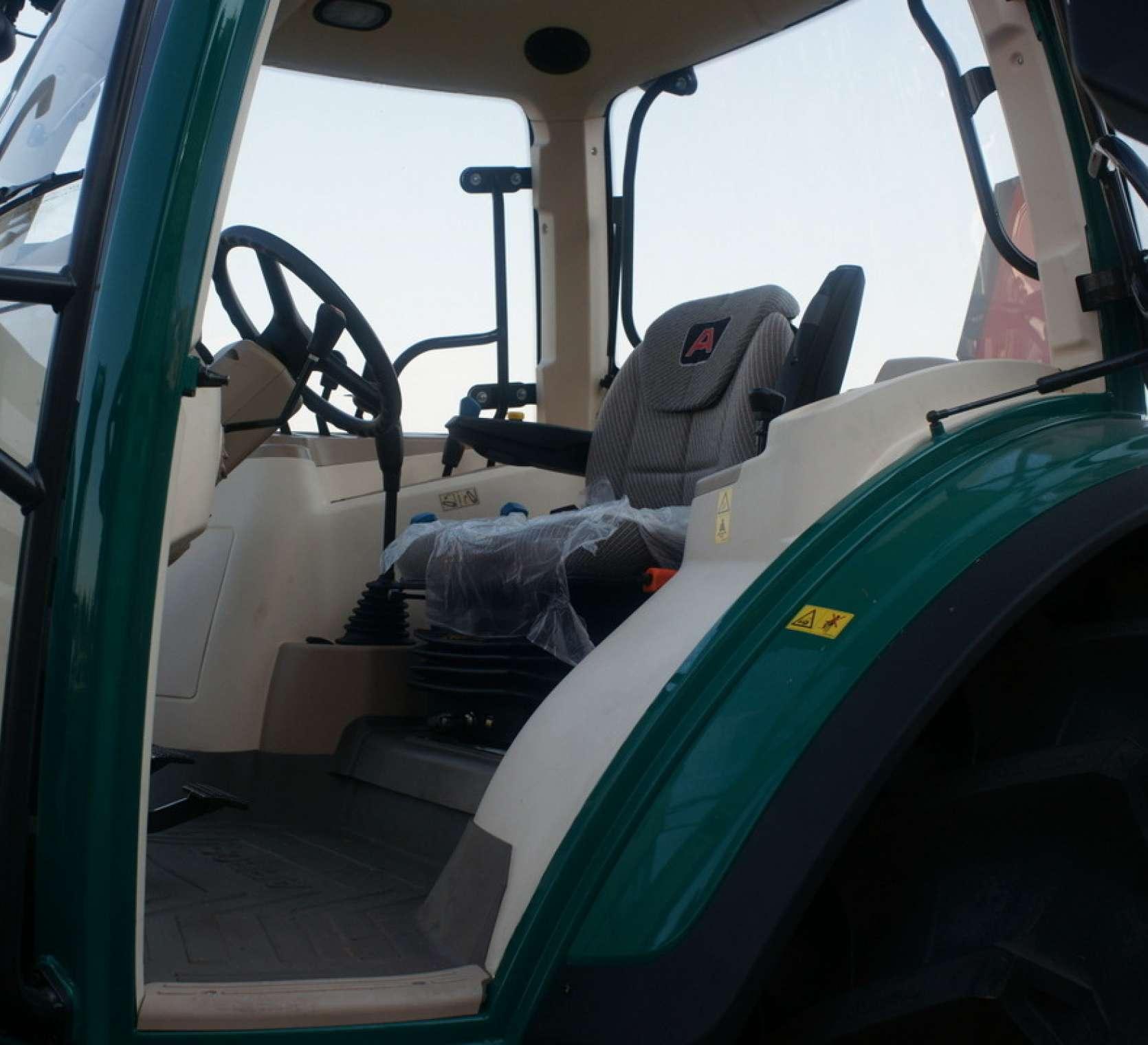 ujecie z boku ciagnika wycentrowane na wnetrze kabiny fotel kolumna kierownicza panel sterowania