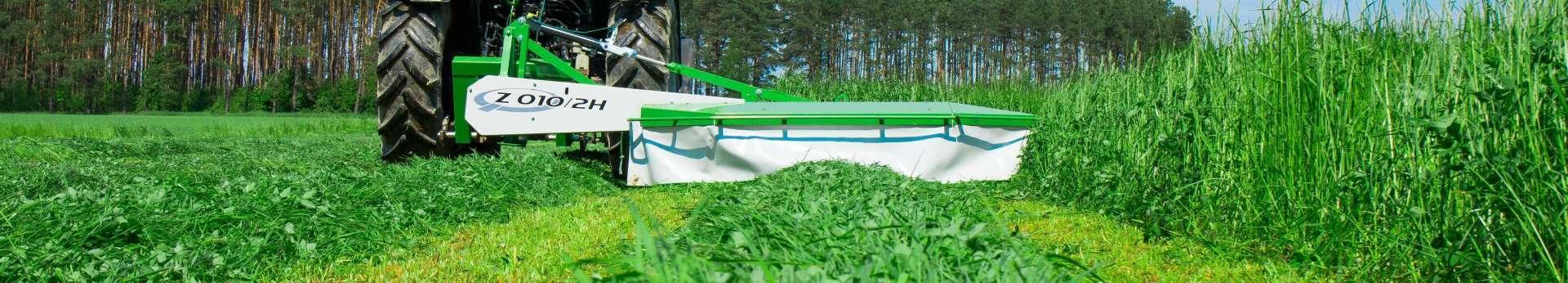 Zielona kosiarka bębnowa zawieszana tylna Z010/2H produkowana przez Samasz kosi trawę na łące. korbanek.pl