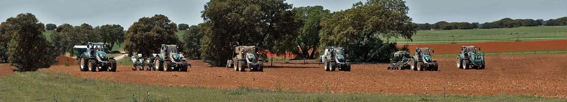 ciągniki rolnicza Arbos Seria 5000 - uniwersalne ciągniki na zdjęciu podczas prac polowych sześć ciągników każdy z inną maszyną