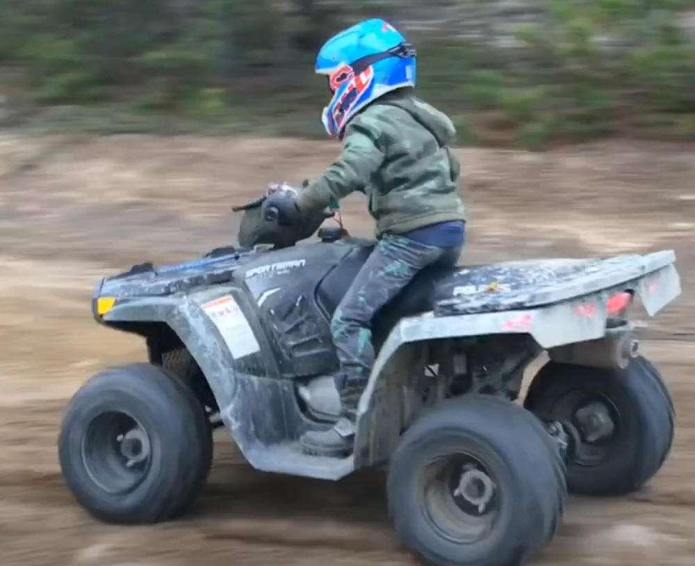 NAuka jazdy quadem Sportsman 110 Polaris kolor niebieski - dziecko w kaski i instruktor podczas nauki