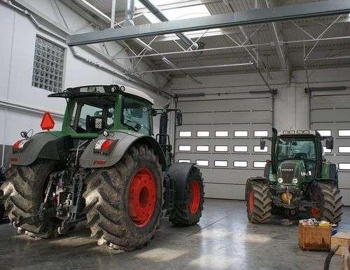 Dwa traktory Fendt w dużej hali warsztatowej