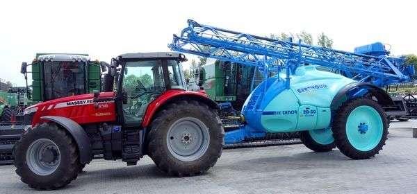 Traktor Massey Ferguson w trakcie transportu z opryskiwaczem Berthoud