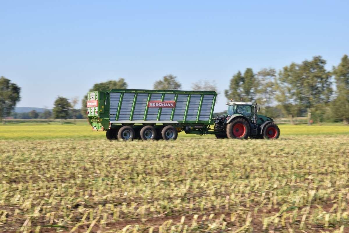 W transporcie widać przyczepę objetościową HTW firmy bergman ciągnie ją ciągnik rolniczy marki FENDT