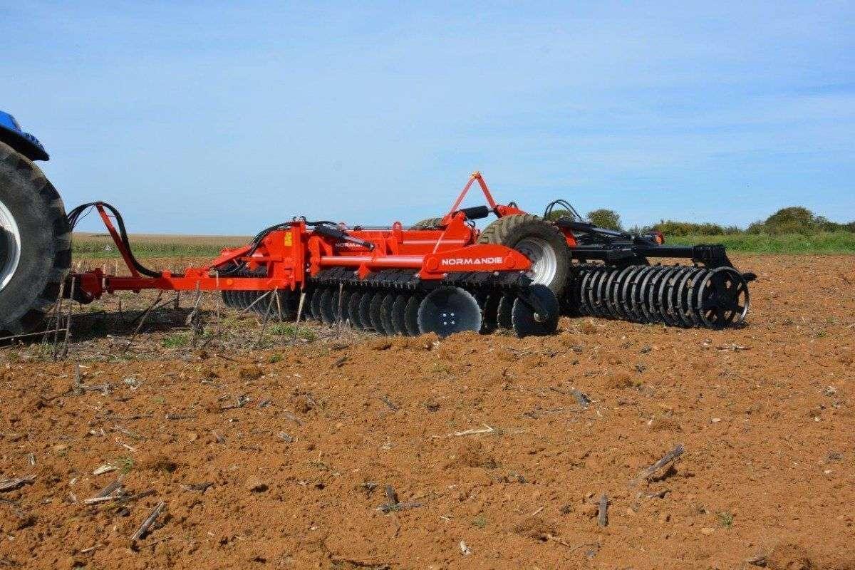 Agregat Gregoire Besson Normandie czerwony zaczepiony do ciągnika na polu podczas pracy