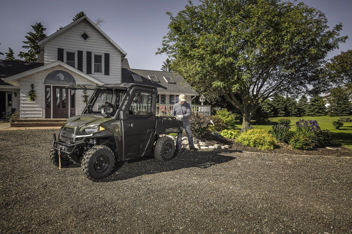 Ciągnik rolniczy RANGER 1000 Xp EPS Polaris z paką załadunkową sojący na tle budynku mieszkalnego