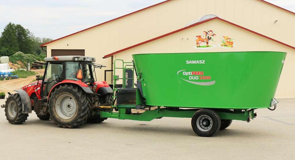 Wóz paszowy DUO firmy Samasz przeznaczony dla dużych gospodarstw. Widok boczny maszyny z ciągnikiem na tle obory