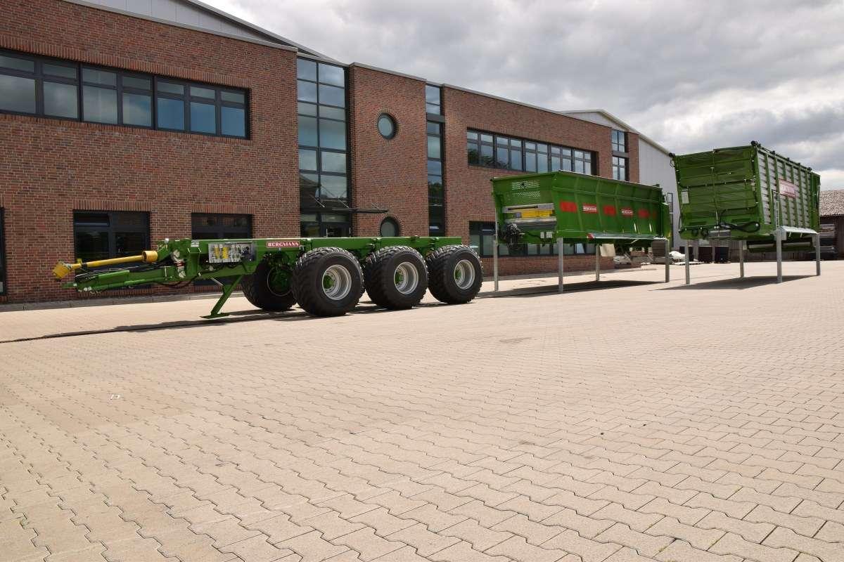 Przyczepa transportow wielofunkcyjna Vario firmy Bergmann na układzie jezdnym tridem wraz z stojącymi obok możliwymi doposażeniami rozrzutnik obornika przyczepa objętościowa